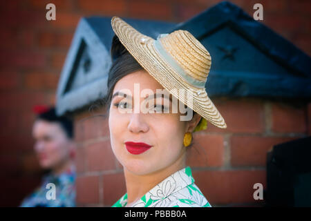 Close-up portrait of stylish lady front view, wearing red lipstick & side-tilted attractive straw hat, Black Country Museum 1940's WWII event. - Stock Photo