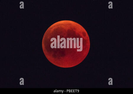 Berlin, Germany. 27th July, 2018. The moon glows in a red color during a full lunar eclipse over Berlin. The phenomenon also known as 'Blood moon' was well observed all across Germany when the moon was covered by Earth's shade. It is also reported that it will be the longest total lunar eclipse of the 21st century. Credit: Omer Messinger/ZUMA Wire/Alamy Live News - Stock Photo