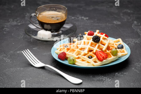 Photo of cup of black coffee with sugar with Viennese waffles with strawberries, raspberries, gooseberries and fork - Stock Photo