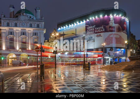 Piccadilly Circus, London-September 8,2017: Light trails from London bus on Piccadilly Circus in rainy early morning time on September 8, 2017 in Lond - Stock Photo