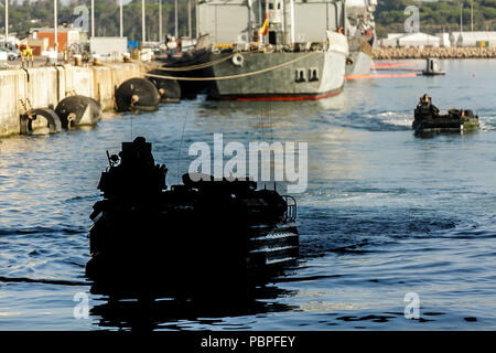 ROTA, Spain (July 20, 2018) U.S. Marines assigned to the Assault Amphibious Vehicle Platoon, Fox Company, Battalion Landing Team, 2nd Battalion, 6th Marine Regiment, 26th Marine Expeditionary Unit (MEU), return to the Harpers Ferry-class dock landing ship USS Oak Hill (LSD 51) after completing a scheduled washdown at Rota, Spain, July 20, 2018. The Oak Hill, homeported in Virginia Beach, Virginia, and the 26th MEU are conducting naval operations in the 6th Fleet area of operations.(U.S. Marine Corps Photo by Staff Sgt. Dengrier M. Baez/Released) - Stock Photo