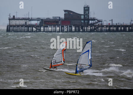 Southend-on-Sea, Essex, UK. Strong winds and rain have hit the south east of the UK. Windsurfers took to the Thames Estuary off Southend - Stock Photo