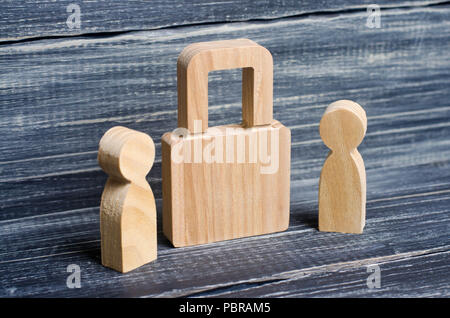 Two people stand near a padlock and keep secrets, information, entrance. Wooden figures of persons carry guards from wicked men, spies. The concept of - Stock Photo
