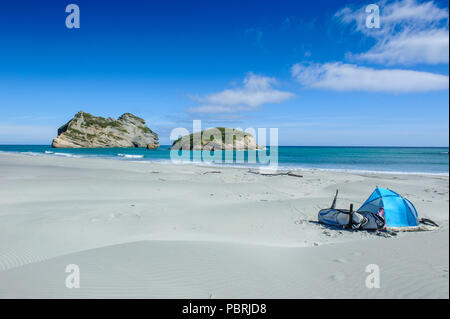 Camping tent on Wharariki Beach with Archway islands in the background, South Island, New Zealand - Stock Photo