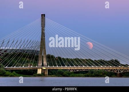 Partial eclipse moon over bridge in Warsaw city in summer time 2018 - Stock Photo