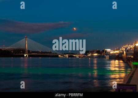 Partial eclipse moon over Vistula river in Warsaw city in summer time 2018 - Stock Photo