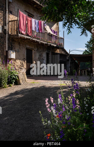 Towels hanging out to dry on the upstairs balcony of a house on the outskirts of Olot, Catalunya, Spain - Stock Photo