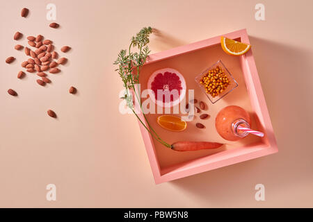 Homemade natural organic smoothie, made with grapefruits, orange, berries, carrots and nuts in glass bottle on an orange paper background. - Stock Photo