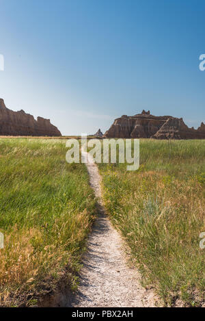 Narrow Dirt Trail Winds Through Field with Badlands Formation - Stock Photo