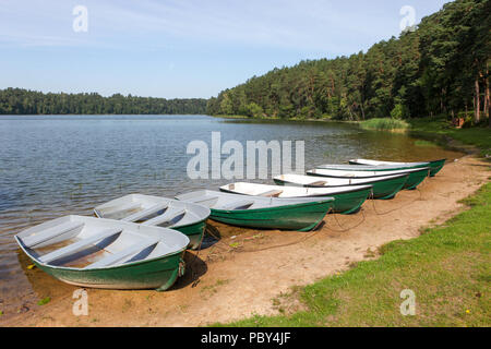 Boats on the beach at Lake Asveja or Dubingiai Lake, the longest lake in Lithuania, with forest on the background - Stock Photo