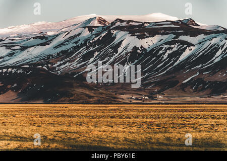 Iceland typical mountain winter scene with grass in foreground and massive mountain in background. - Stock Photo