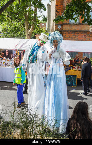 Man and woman on stilts dressed in white costumes at the 'Fair in the Square', an annual festival in Highgate Village, London, UK - Stock Photo