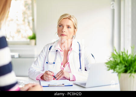 Shot of female doctor talking to woman and discussing about medical report at the doctor's room. - Stock Photo