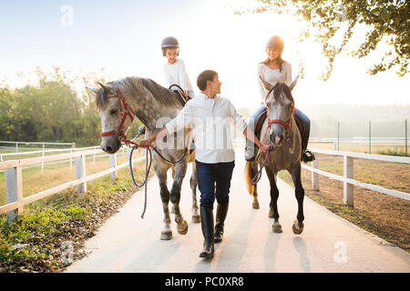 Cheerful young Chinese family riding horses - Stock Photo