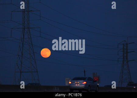 Moonrise over highway in Texas - Stock Photo