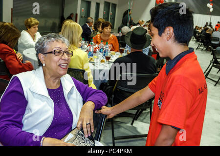 Miami Beach Florida Convention Center centre Seniors Holiday Party senior Hispanic volunteer student serving dinner banquet free event Hispanic woman - Stock Photo