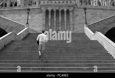 Man walking up the stairs of Fishermen's Bastion in Budapest while a man is painting in the background - Stock Photo