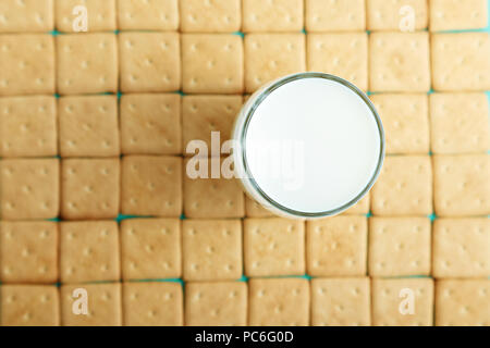lots of crackers, appetizing background. square crackers are laid out in rows,  on the crackers there is a glass with milk - Stock Photo
