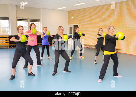 Group of seven women in gym class training with balls - Stock Photo