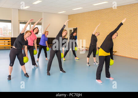 Group of women with balls doing stretching exercises in gym class - Stock Photo