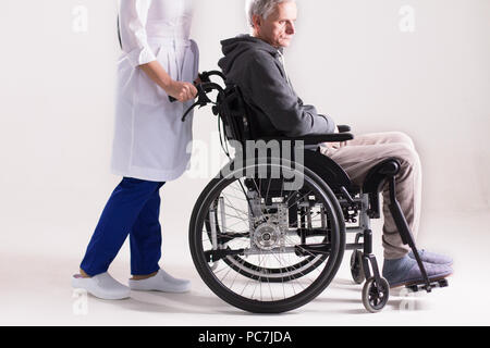 Studio shot of doctor pushing wheelchair with man it. Cropped picture of doctor in white coat and blue pants pushing wheelchair with elderly man sitti - Stock Photo