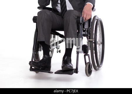 Cropped picture of disbaled man insuit. Studio shot of man sitting in wheelchair wearing fancy business outfit. - Stock Photo