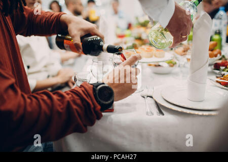 A man pours red wine into a glass - Stock Photo