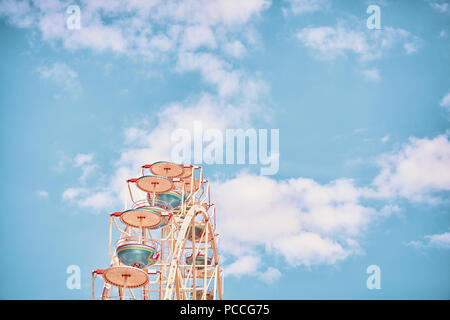Retro stylized picture of a Ferris wheel against sky, space for text. - Stock Photo