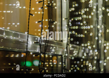 Festive dark blurred background with bokeh lights, electric garland and house. - Stock Photo