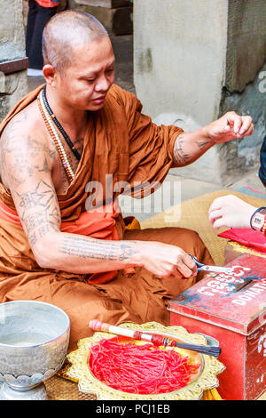 Angkor Wat, Cambodia - 11th January 2018: Monk giving blessings and tying good luck string bracelets. This is in exchange for donations. - Stock Photo