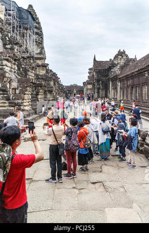 Angkor Wat, Cambodia - 11th January 2018: Chinese tourists pose for photos, Huge numbers visit the temple complex - Stock Photo