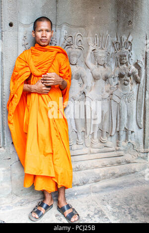 Angkor Wat, Cambodia - 11th January 2018: Monk stood by a bas relief picture. Monks can often be seen around the complex. - Stock Photo