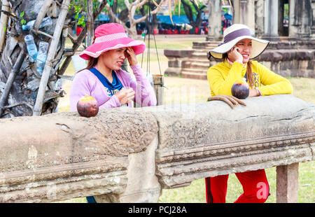 Angkor Wat, Cambodia - 11th January 2018: Two Cambodian girl vendors wearing hats. There are many vendors around the complex. - Stock Photo