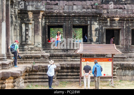 Angkor Wat, Cambodia - 11th January 2018: Chinese tourists posing for photos. They show liitle respect for ancient ruins. - Stock Photo