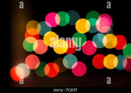 Blurred bokeh colorful lights lanterns, holiday new year lighting on black background Christmas winter glitter shiny light bokeh in rainbow colors. - Stock Photo