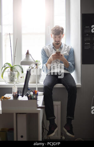 Young stylish man sitting on the window with phone in hands - Stock Photo