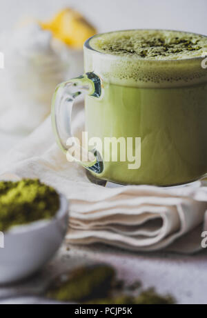 BULLETPROOF MATCHA. Ketogenic keto diet hot drink. Tea matcha blended with coconut oil and butter. Cup of bulletproof matcha and ingredients on white background - Stock Photo
