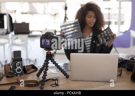 Pretty photographer working at laptop - Stock Photo