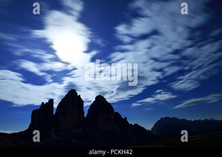 North walls of the Three Peaks of Lavaredo at full moon night, Sexten Dolomites, Hochpustertal valley, South Tyrol, Italy - Stock Photo