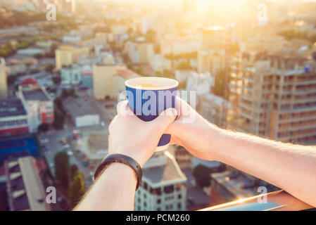 Close up man's hands holding take away paper cup with morning hot drink - coffee or tea with inspiring view on abstract city background at sunrise or sunset. Soft selective focus. Copy space. - Stock Photo