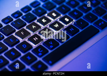 Fake news written on a backlit laptop keyboard close-up with selective focus in a blue ambiant light - Stock Photo