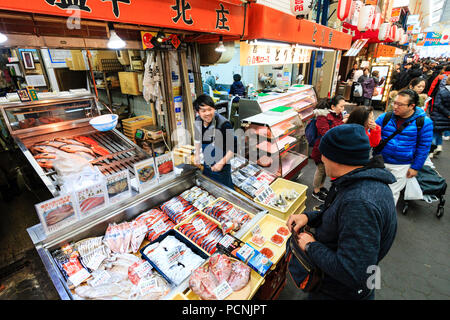 Kuromon Ichiba, food market in Osaka. Fish monger stall with fish potions, overhead view, assistant talking to customer, motion blur. Arcade busy. - Stock Photo