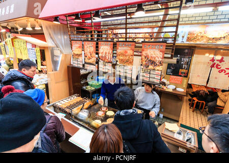 Kuromon Ichiba, food market in Osaka. Overhead view of Japanese fast food diner with chef cooking okonomiyaki on hot plate while customers wait. - Stock Photo