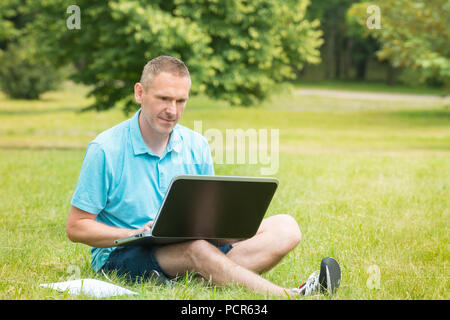 Man sitting on grass in the park and working on his laptop - Stock Photo
