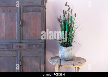 Old vase with flowers on vintage round wooden table - Stock Photo