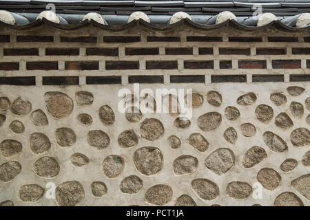 A traditional Korean residential wall constructed with stone blocks, rocks and mud, at Bukchon Hanok Village, Seoul, South Korea. - Stock Photo
