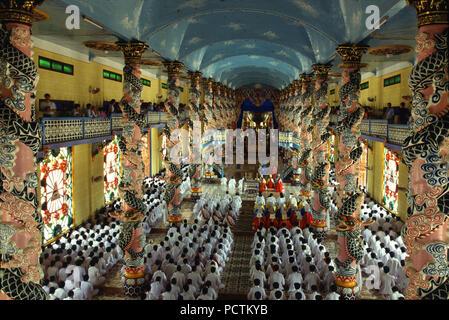 People praying in Cao Dai temple, Tay Ninh, Vietnam, Indochina - Stock Photo