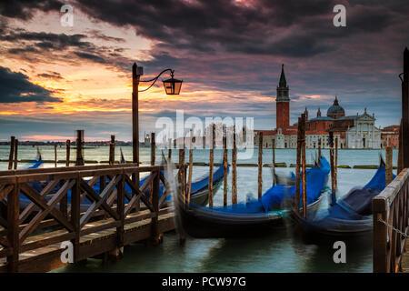 Parked gondolas in Venice with the island of San Giorgio Maggiore in the background - Stock Photo