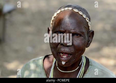TAMBERMA VIL, TOGO - JAN 13, 2017: Unidentified Tammari an old woman with a canine under her lower lip talks in the village. Tammaris are ethnic group - Stock Photo