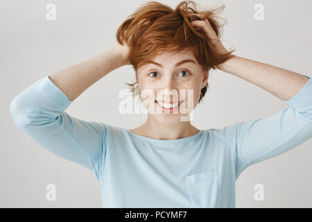 Girl likes her short haircut. Indoor shot of happy carefree redhead woman with freckles holding hands on hair and smiling broadly, making hairstyle lo - Stock Photo